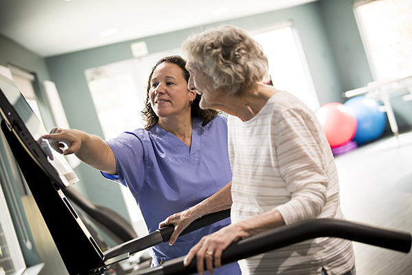 Nurse with woman on balance machine