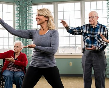 Blog11 - Woman guides group of seniors in dance activity